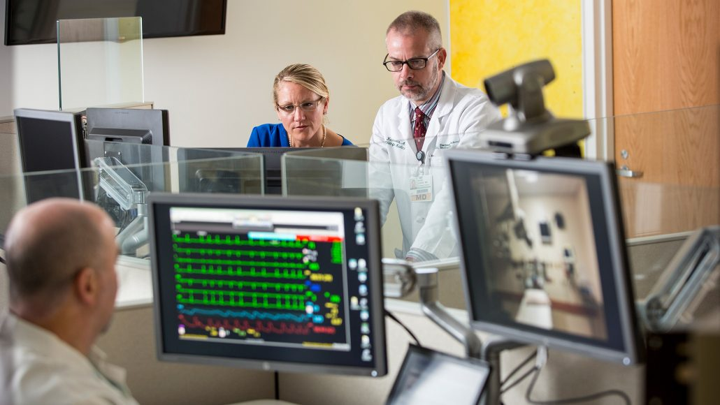 Mark Pippy (foreground), Michelle Buck, and Kevin Curtis work with a remote bedside team to monitor a patient's vital signs in DHMC's Connected Care Center for Telehealth. Photo by Mark Washburn